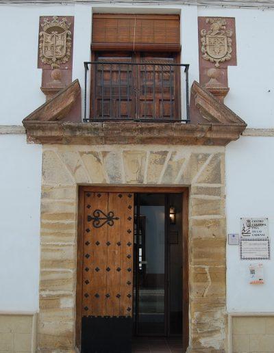 Casa de las cadenas. Destaca, en su portada barroca, el empleo de la piedra molinaza. Presenta dintel partido con dos plintos